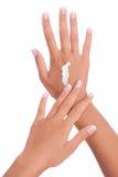 Mãos que aplicam o creme Imagens de Stock