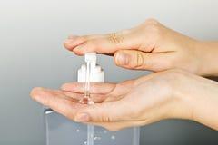 Mãos que aplicam o gel do sanitizer fotografia de stock royalty free
