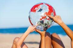 Mãos que apontam na bola inflável da terra Fotografia de Stock Royalty Free