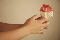 Mãos que balançam uma casa pequena foto de stock