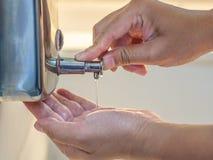 Mãos que bombeiam o sabão no toalete para a lavagem as mãos Limpar, fotos de stock