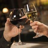 Mãos que brindam o vinho. Imagem de Stock