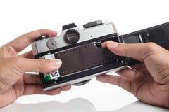 Mãos que carregam o filme na câmera Fotografia de Stock