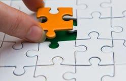 Mãos que colocam a parte de um enigma foto de stock