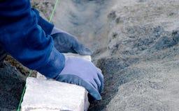Mãos que colocam a pedra na terra imagens de stock