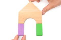 Mãos que compõem uma casa com o trajeto de grampeamento Imagens de Stock
