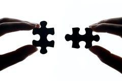 Mãos que conectam partes do enigma de serra de vaivém Foto de Stock