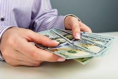 Mãos que contam o dinheiro foto de stock