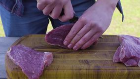 Mãos que cortam a carne usando uma faca em uma parte externa de superfície de madeira filme