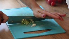 Mãos que cortam cebolas da mola nas partes filme