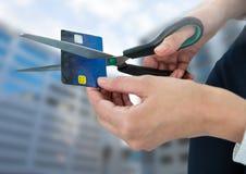 Mãos que cortam o cartão de banco com construções Fotografia de Stock Royalty Free