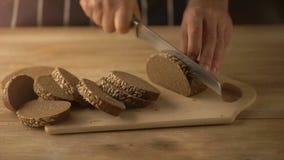 Mãos que cortam o pão com a faca na tabela de madeira rústica video estoque