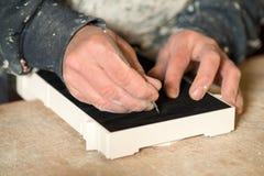 Mãos que cortam o papel de feltro do preto em um modelo do emplastro Fotografia de Stock