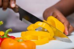 Mãos que cortam pimentas de sino com faca, preparação dos alimentos foto de stock