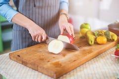 Mãos que cortam uma maçã na placa de desbastamento Jovem mulher que prepara uma salada de fruto em sua cozinha Imagens de Stock