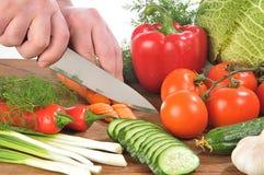 Mãos que cortam vegetais imagem de stock royalty free