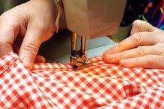 Mãos que costuram o pano da sarja de Nimes com uma máquina de costura Foto de Stock Royalty Free