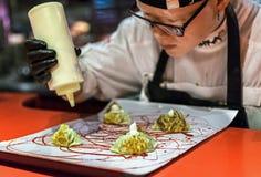 Mãos que cozinham o prato gourmet As bolinhas de massa do pequinês do porco da orelha serviram com molho de hoisin e foto de stock