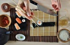 Mãos que cozinham o sushi fotografia de stock