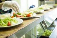 Mãos que cozinham a salada dos vegetais Fotos de Stock Royalty Free
