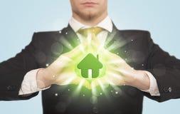 Mãos que criam um formulário com a casa verde Foto de Stock Royalty Free