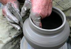 Mãos que dão forma à argila na roda de oleiro Fotografia de Stock Royalty Free