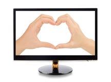 Mãos que dão forma a um coração no monitor Fotografia de Stock Royalty Free