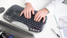 Mãos que datilografam em um teclado Fotografia de Stock