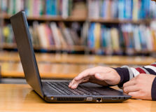 Mãos que datilografam no caderno na biblioteca Fotografia de Stock
