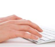 Mãos que datilografam no teclado de computador sem fio remoto Imagens de Stock Royalty Free