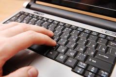 Mãos que datilografam no teclado do computador portátil fotografia de stock royalty free