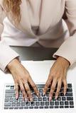 Mãos que datilografam no teclado do portátil fotografia de stock