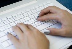 Mãos que datilografam no teclado do portátil fotografia de stock royalty free