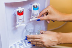 Mãos que derramam a água do refrigerador Imagem de Stock