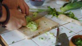 Mãos que desbastam vegetais na placa de corte de madeira vídeos de arquivo