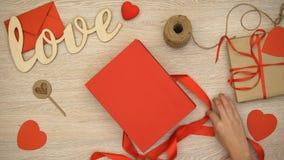 Mãos que desembalam o giftbox com os doces de chocolate coração-dados forma, surpresa dos Valentim filme