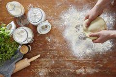 Mãos que desenrolam a farinha atmosférica da cena da cozinha da massa e o espaço de trabalho de madeira Foto de Stock Royalty Free