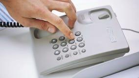 Mãos que discam o número em telefone ajustado da mesa no escritório filme