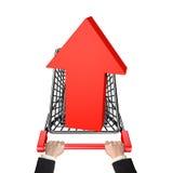 Mãos que empurram o carrinho de compras com a seta 3D vermelha acima do símbolo Foto de Stock