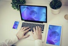 mãos que escrevem em um portátil com tabuleta e telefone Fotos de Stock