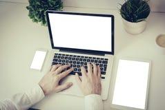 mãos que escrevem em um portátil com tabuleta e telefone Foto de Stock Royalty Free