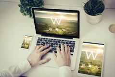 mãos que escrevem em um portátil com tabuleta e telefone w Imagens de Stock