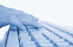Mãos que escrevem em um teclado de computador foto de stock