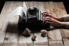 Mãos que escrevem na máquina de escrever velha sobre a tabela de madeira Fotos de Stock Royalty Free
