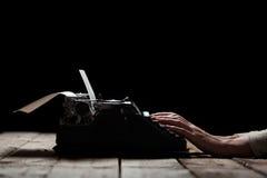 Mãos que escrevem na máquina de escrever velha sobre a tabela de madeira fotos de stock