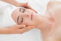 Mãos que fazem massagens a cara da mulher em termas da beleza Fotos de Stock