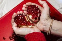 Mãos que fazem um coração de partes da romã na placa de corte vermelha fotos de stock
