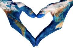 Mãos que formam um coração modelado com um mapa do mundo (fornecido por N imagem de stock royalty free