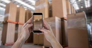 Mãos que fotografam caixas através do telefone esperto no armazém Foto de Stock