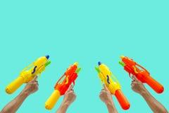 Mãos que guardam a arma de água colorida para o festival da água ou do Songkran foto de stock